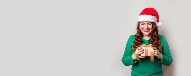 Szczęśliwa uśmiechnięta kobieta w czerwonym santa kapeluszu i zielonym pulowerze trzyma niespodzianki prezenta pudełko z złocistym faborkiem na szarości z miejscem dla teksta.