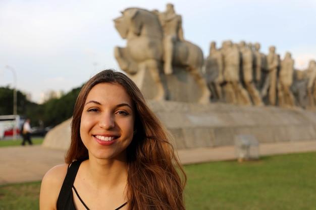 Szczęśliwa uśmiechnięta kobieta w sao paulo z pomnikiem punktu orientacyjnego bandeiras