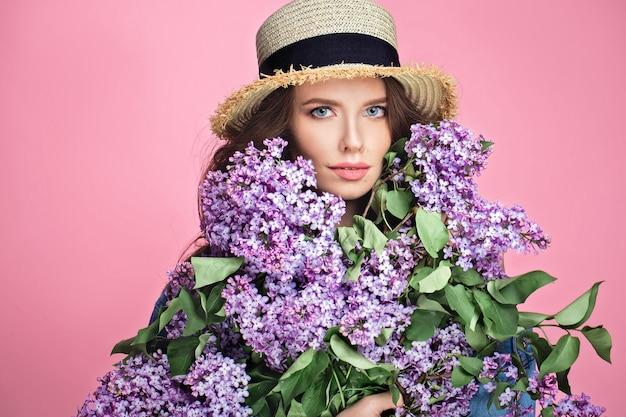 Szczęśliwa uśmiechnięta kobieta w słomianym kapeluszu pozuje z bukietem lili kwiaty