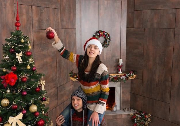 Szczęśliwa uśmiechnięta kobieta w śmiesznym kapeluszu siedzi na szyi swojego chłopaka i zawiesza dekorację na dużej choince w ich salonie z udekorowanym kominkiem