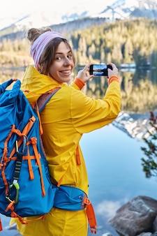 Szczęśliwa uśmiechnięta kobieta w swobodnym płaszczu przeciwdeszczowym, nosi plecak