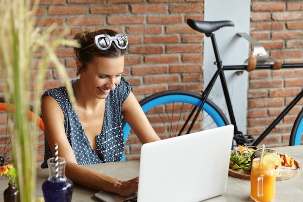 Szczęśliwa uśmiechnięta kobieta wysyła wiadomości do przyjaciół online w mediach społecznościowych, przegląda internet, korzysta z bezpłatnego wi-fi na swoim nowoczesnym laptopie, siedzi przy stole z jedzeniem. ludzie