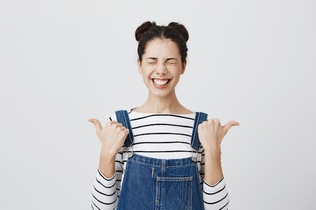 Szczęśliwa uśmiechnięta kobieta z zamkniętymi oczami, wskazując palcami w lewo i prawo