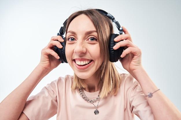 Szczęśliwa uśmiechnięta kobieta ze słuchawkami do słuchania muzyki
