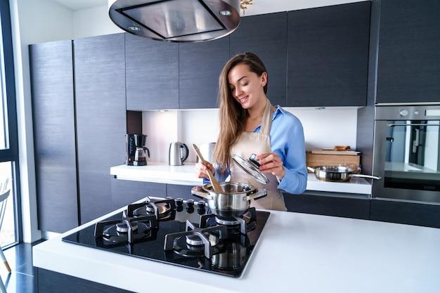 Szczęśliwa uśmiechnięta kulinarna kobiety gospodyni domowa w fartuchu używa stalowego metalu rondel dla przygotowywać gotowanych naczynia dla gościa restauracji w kuchni w domu. artykuły kuchenne do gotowania