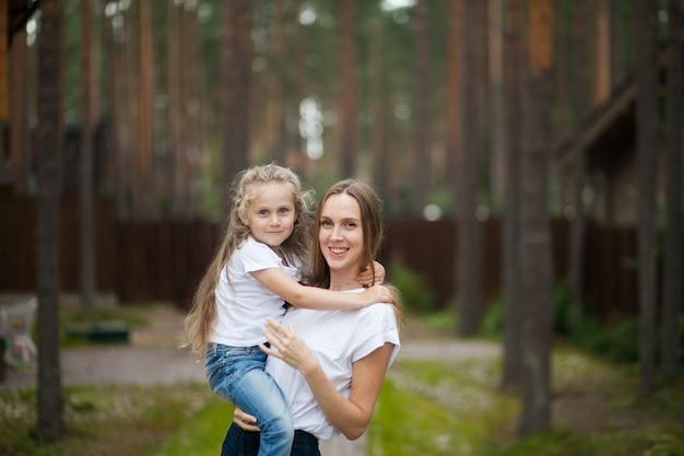 Szczęśliwa uśmiechnięta matka i przytulanie śliczna emocjonalna córeczka