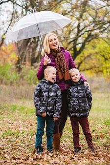 Szczęśliwa uśmiechnięta matka trzyma męskie bliźniaki pod parasolem podczas deszczowej jesiennej pogody w kolorowym parku