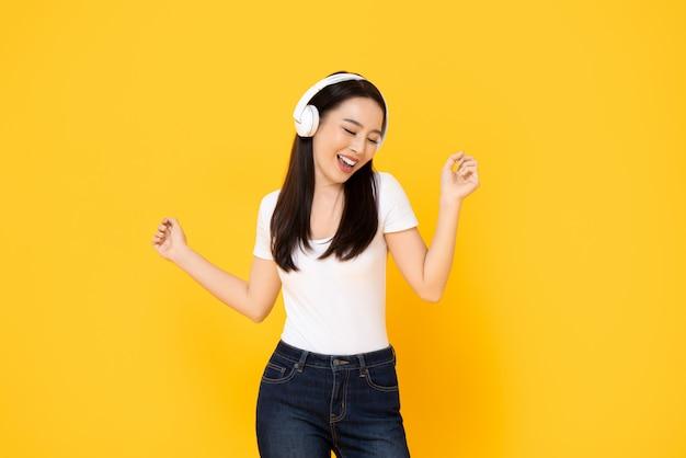 Szczęśliwa uśmiechnięta młoda azjatycka kobieta słucha muzyka od hełmofonów i tana