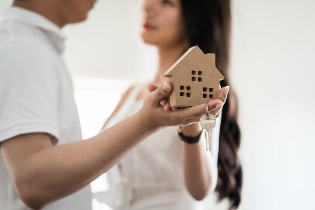 Szczęśliwa uśmiechnięta młoda azjatycka para trzymająca modelowy dom