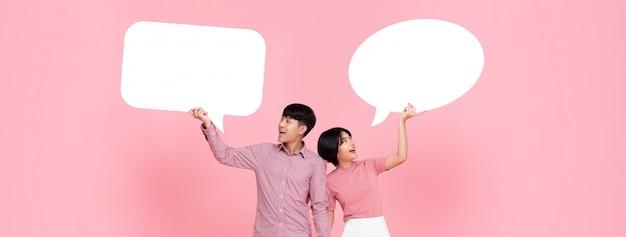 Szczęśliwa uśmiechnięta młoda azjatycka para z mowa bąblami
