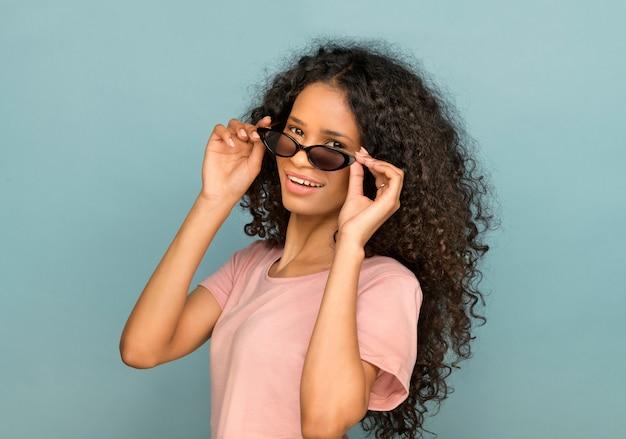 Szczęśliwa uśmiechnięta młoda czarna kobieta z opuszczonymi cieniami, okularami przeciwsłonecznymi lub okularami przeciwsłonecznymi