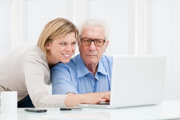 Szczęśliwa uśmiechnięta młoda dziewczyna wyjaśnia i uczy jej dziadków korzystania z nowoczesnego komputera
