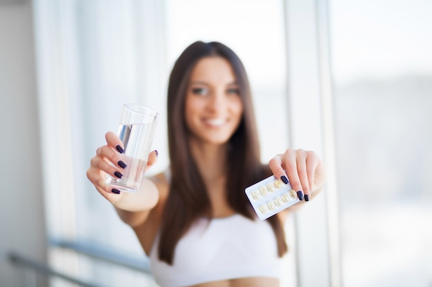 Szczęśliwa uśmiechnięta młoda kobieta bierze dietetycznego nadprogram