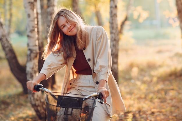 Szczęśliwa uśmiechnięta młoda kobieta jazda na rowerze vintage w parku jesień o zachodzie słońca