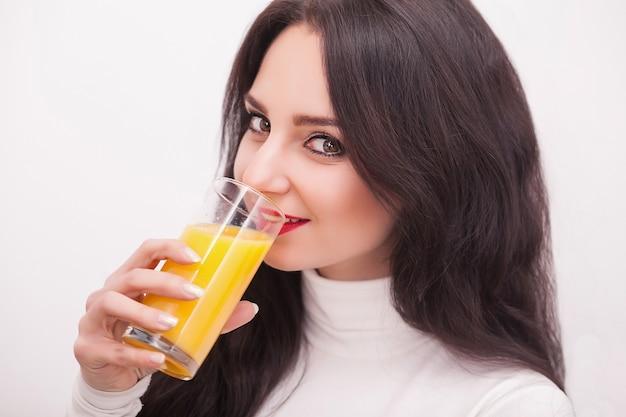 Szczęśliwa uśmiechnięta młoda kobieta pije sok pomarańczowy
