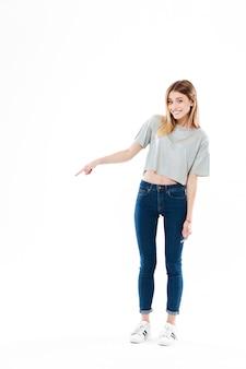 Szczęśliwa uśmiechnięta młoda kobieta stoi i wskazuje