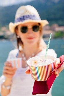 Szczęśliwa uśmiechnięta młoda kobieta trzyma papierowe kubki z lodami w okularach przeciwsłonecznych w gorący słoneczny letni dzień na plaży.