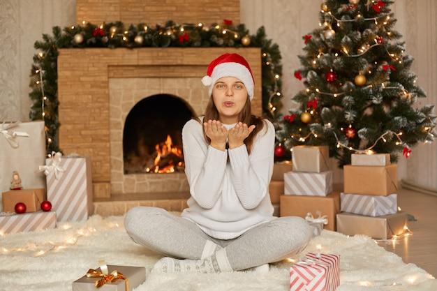 Szczęśliwa uśmiechnięta młoda kobieta w czapce mikołaja wysyłająca pocałunek na lampki choinkowe i kominek w domu pani w białym swetrze z zaokrąglonymi ustami siedzi ze skrzyżowanymi nogami na podłodze.