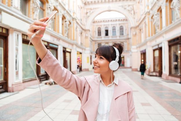 Szczęśliwa uśmiechnięta młoda kobieta w hełmofonach robi selfie fotografii