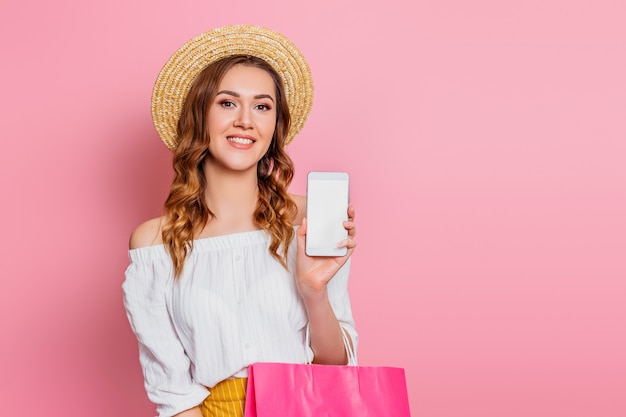 Szczęśliwa uśmiechnięta młoda kobieta w słomianym kapeluszu i biel sukni z torba na zakupy pozować odizolowywam na menchii ścianie. dziewczyna trzyma smartphone w ręce makieta pusty ekran przestrzeń dla projektu