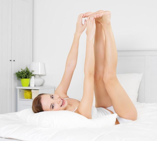Szczęśliwa uśmiechnięta młoda kobieta z pięknymi nogami, leżąc na łóżku w sypialni