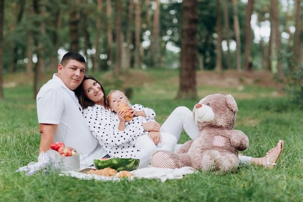 Szczęśliwa uśmiechnięta młoda rodzina na pinkinie w parku przy letnim dniem. pojęcie wakacji letnich. dzień ojca, matki, dziecka. spędzać razem czas. selektywna ostrość