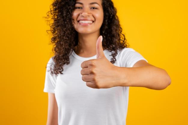 Szczęśliwa uśmiechnięta murzynka pokazuje aprobaty odizolowywać nad kolorem żółtym