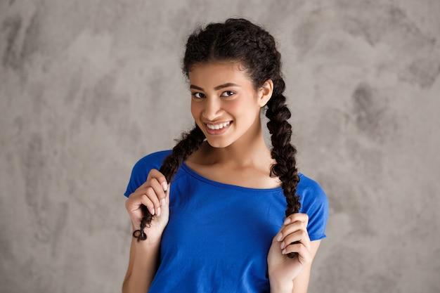 Szczęśliwa uśmiechnięta nastoletnia kobieta z warkoczami