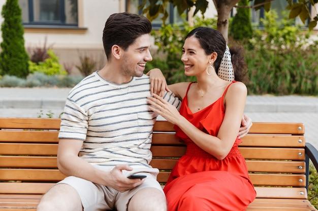Szczęśliwa uśmiechnięta para korzystająca z telefonu komórkowego i przytulająca się, siedząc na ławce na zielonej ulicy
