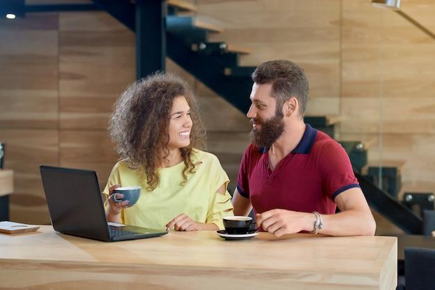 Szczęśliwa uśmiechnięta para patrzeje each inny pije kawę w kawiarni.