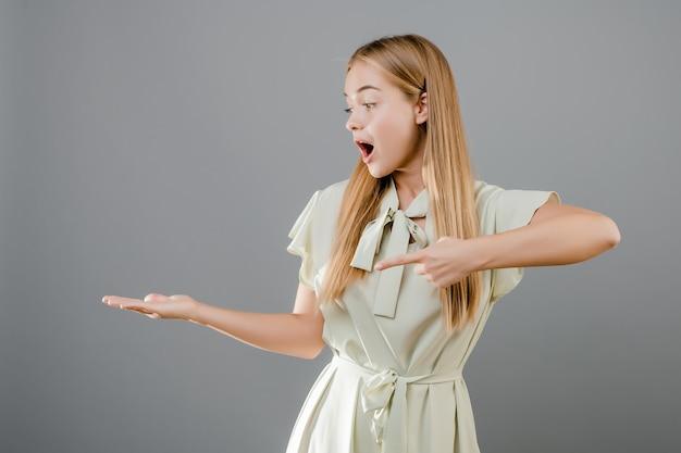Szczęśliwa uśmiechnięta piękna blondynki młoda kobieta wskazuje palec przy copyspace odizolowywającym nad popielatym