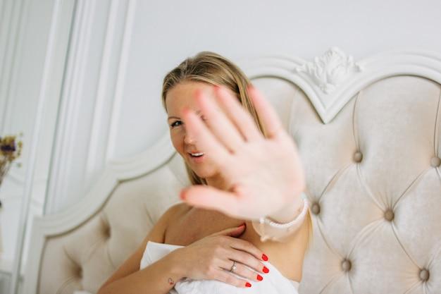 Szczęśliwa uśmiechnięta piękna długie włosy młodej kobiety ciągnięcia ręka w kierunku kamery obsiadania na łóżku, selekcyjna ostrość na ręce