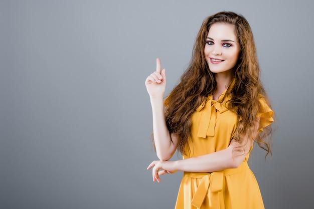 Szczęśliwa uśmiechnięta piękna dziewczyna wskazuje up przy copyspace