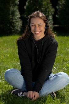 Szczęśliwa uśmiechnięta piękna kobieta w słuchawkach mruga, siedząc na trawie na zewnątrz
