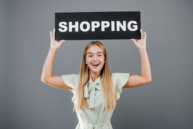 Szczęśliwa uśmiechnięta piękna kobieta z zakupy znakiem odizolowywającym nad popielatym