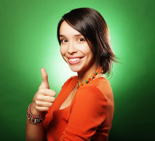 Szczęśliwa uśmiechnięta piękna młoda kobieta pokazując kciuk w górę gest
