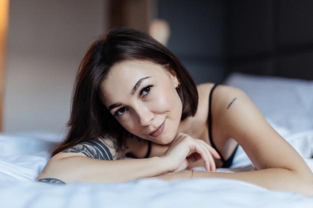 Szczęśliwa uśmiechnięta piękna młoda kobieta w łóżku w wczesnym poranku