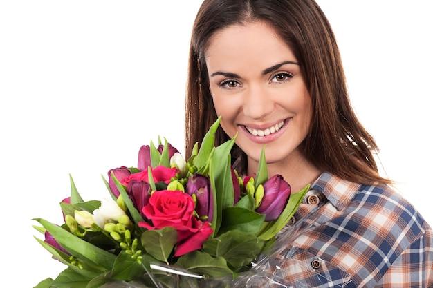 Szczęśliwa uśmiechnięta piękna młoda kobieta z bukietem