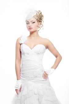Szczęśliwa uśmiechnięta piękna panna młoda w białej sukni ślubnej z fryzurą i jasnym makijażem