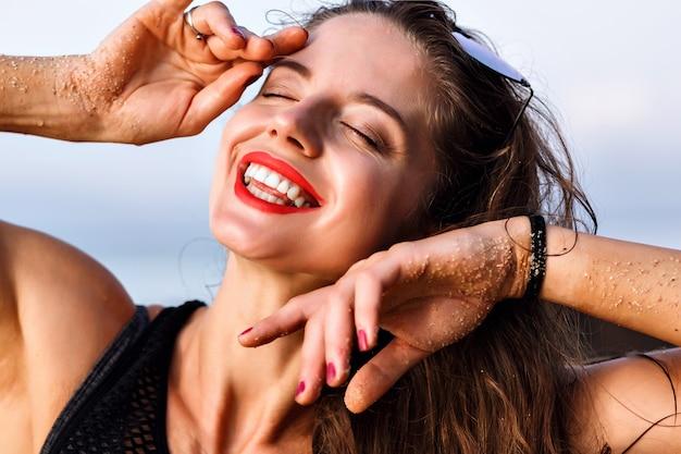 Szczęśliwa uśmiechnięta pozytywna kobieta bawi się i ciesz się latem, portret z bliska, idealna skóra i naturalny makijaż, relaksująca koncepcja.