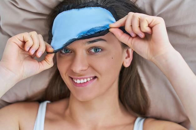 Szczęśliwa uśmiechnięta radosna śpiąca kobieta za pomocą maski na oczy dla lepszego snu i słodkich snów