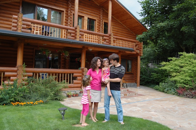 Szczęśliwa uśmiechnięta rodzina blisko drewnianego domu
