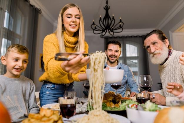 Szczęśliwa uśmiechnięta rodzina, dziadek, rodzice i dzieci siedzi przy świątecznym stole i je smaczny obiad