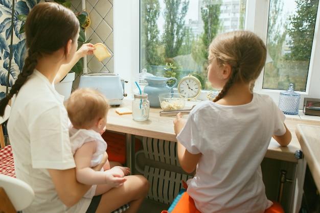 Szczęśliwa uśmiechnięta rodzina kaukaska w kuchni podczas śniadania w domu. styl życia, szczęście, koncepcja rodziny. mama i dwie córki siedzą razem