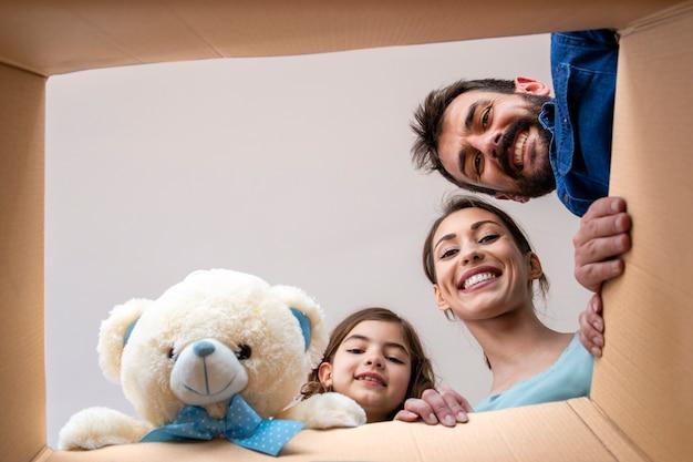 Szczęśliwa uśmiechnięta rodzina otwierająca karton i rozpakowująca rzeczy w nowym domu