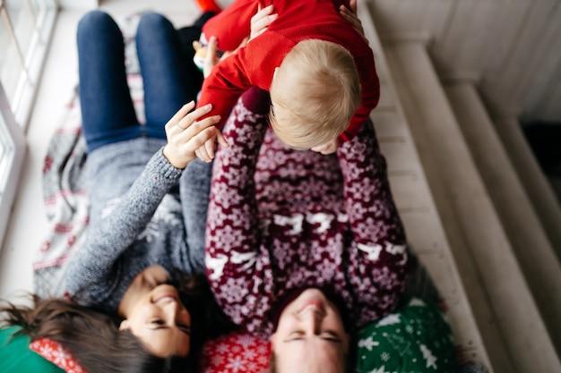 Szczęśliwa uśmiechnięta rodzina przy studiiem na tle choinka z prezentem
