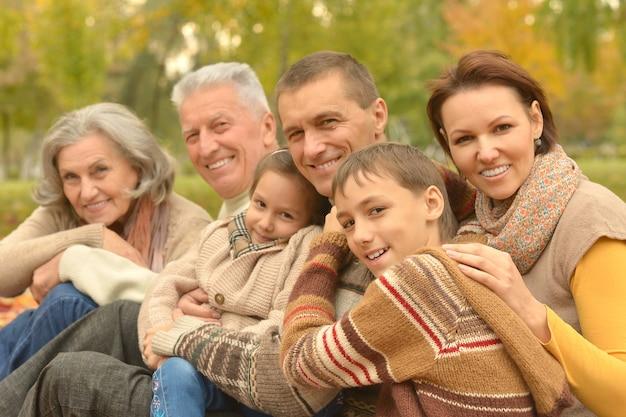 Szczęśliwa uśmiechnięta rodzina relaksuje się w jesiennym parku