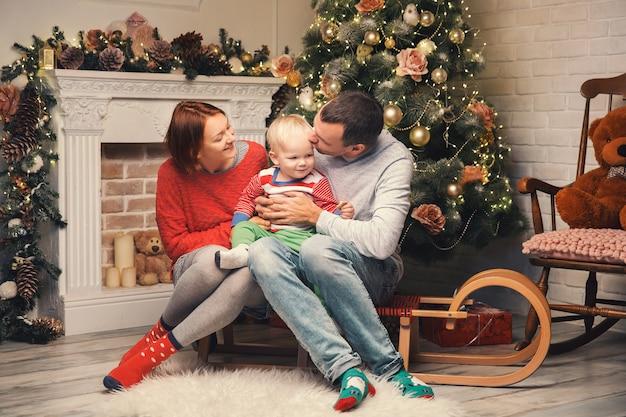Szczęśliwa uśmiechnięta rodzina we wnętrzu domu na tle choinki z prezentami