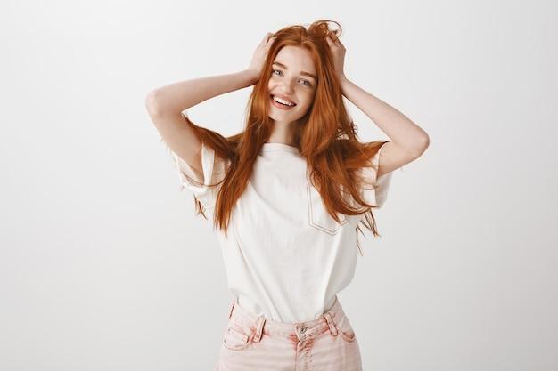 Szczęśliwa uśmiechnięta ruda dziewczyna dotyka jej włosów