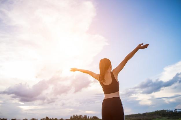 Szczęśliwa uśmiechnięta sportowa kobieta z rękami szeroko rozpościerać